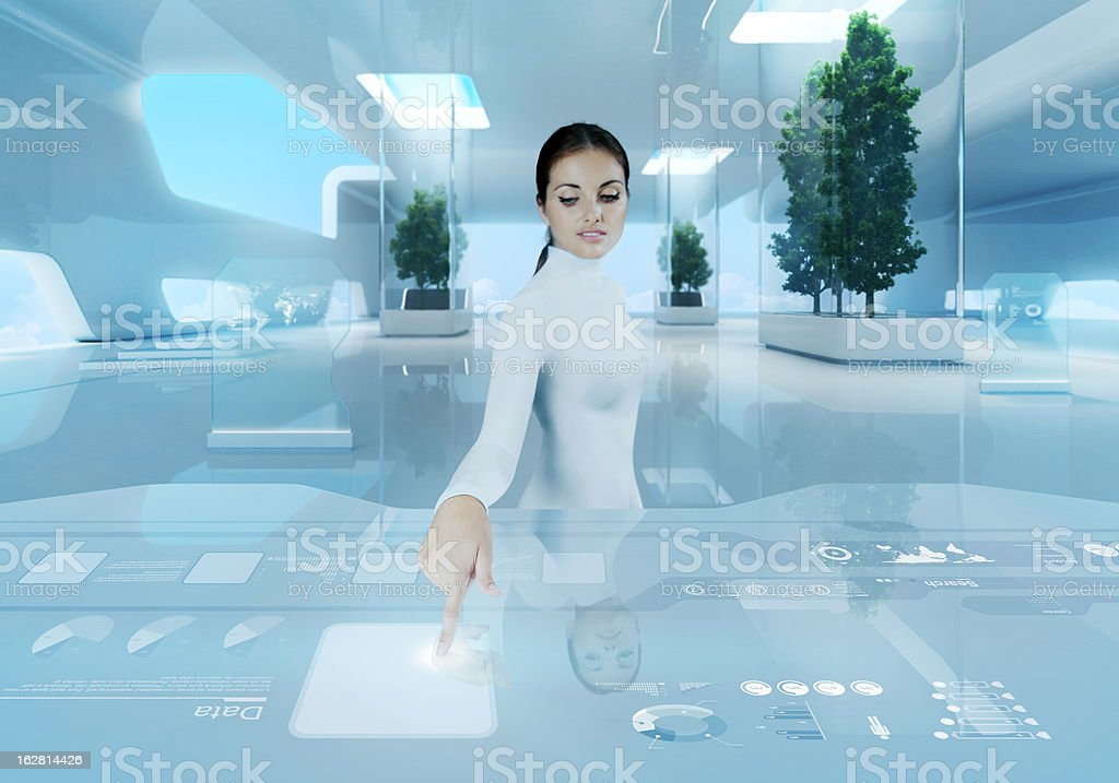 Woman pressing virtual button in futuristic office royalty-free stock photo