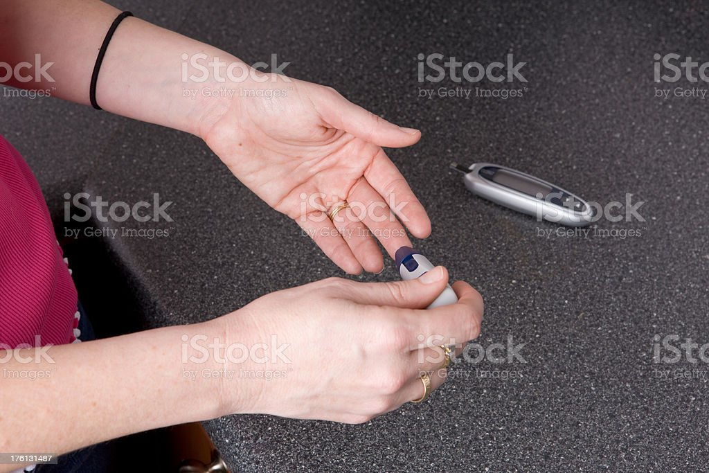 Woman Pricks Her Finger For Blood Sugar Test royalty-free stock photo