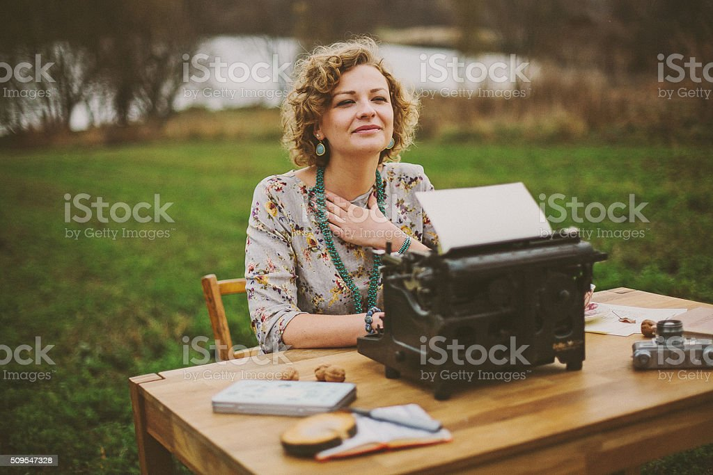 Woman prints on old vintage typewriter stock photo