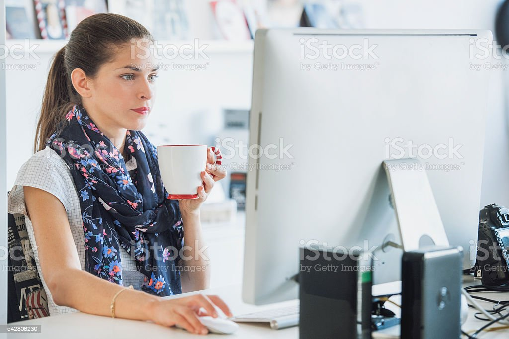 Woman professional is using a computer drinking a beverage stock photo