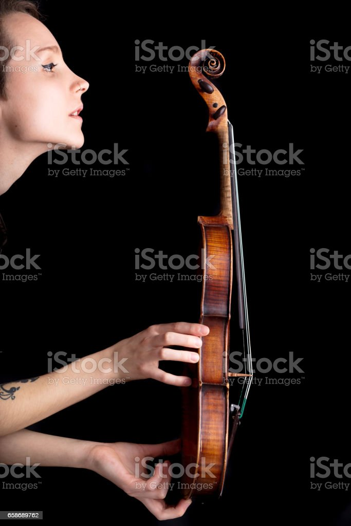 woman profile and violin on black background stock photo