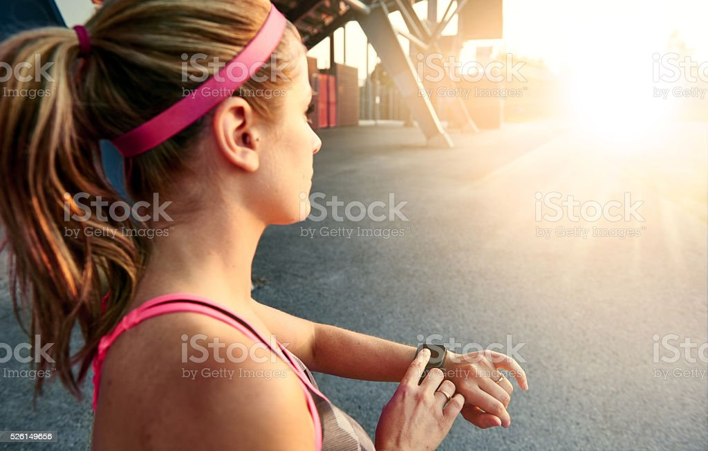 Woman programming her smartwatch before going jogging to track performance stock photo