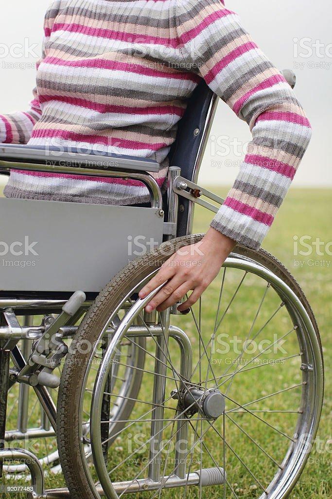 Woman propelling wheelchair stock photo