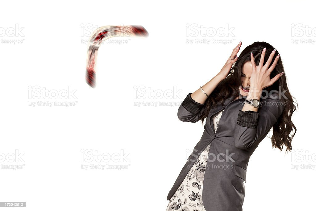 Woman protecting her face from an incoming boomerang stock photo