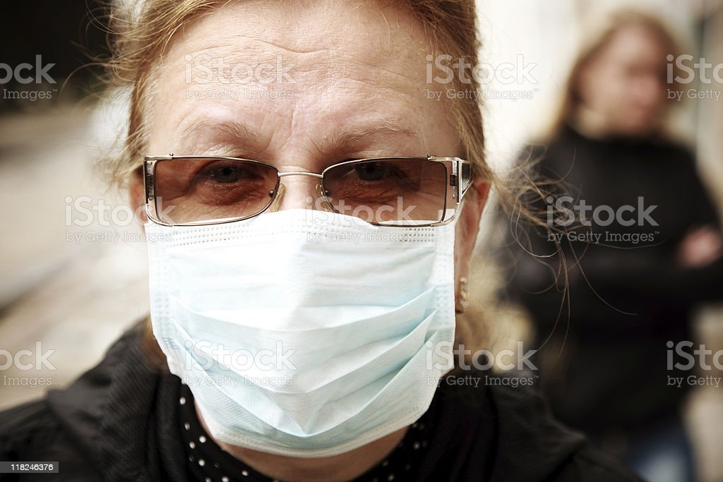 woman protecting herself against influenza with a face mask stock photo