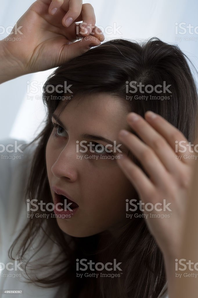 Woman pulling a gray hair stock photo