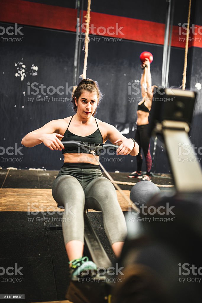 Woman pulling at the rowing machine stock photo