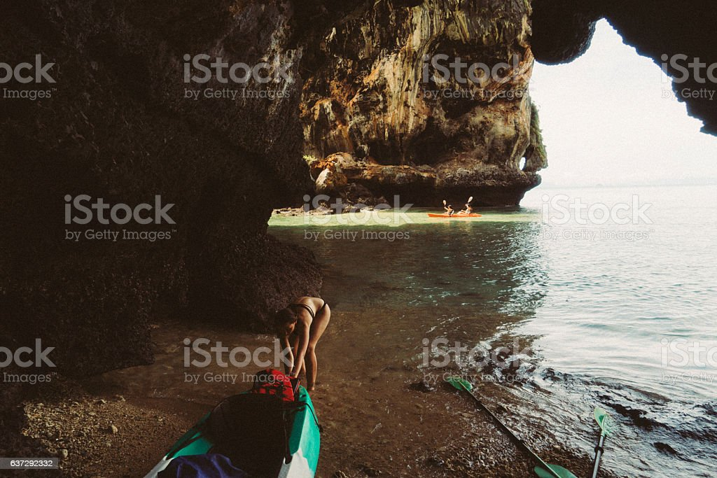 Woman pulling kayak  into the water stock photo