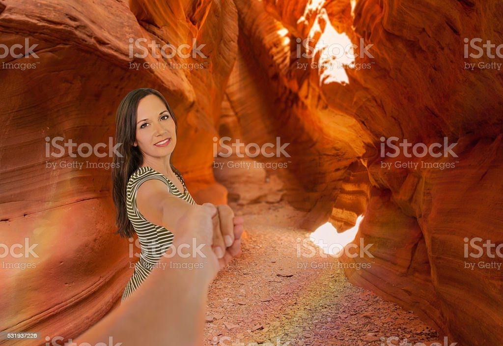 Woman pulling man down narrows red rock trail stock photo