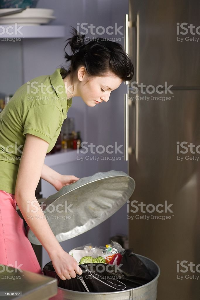 Woman pulling out rubbish bag from bin stock photo