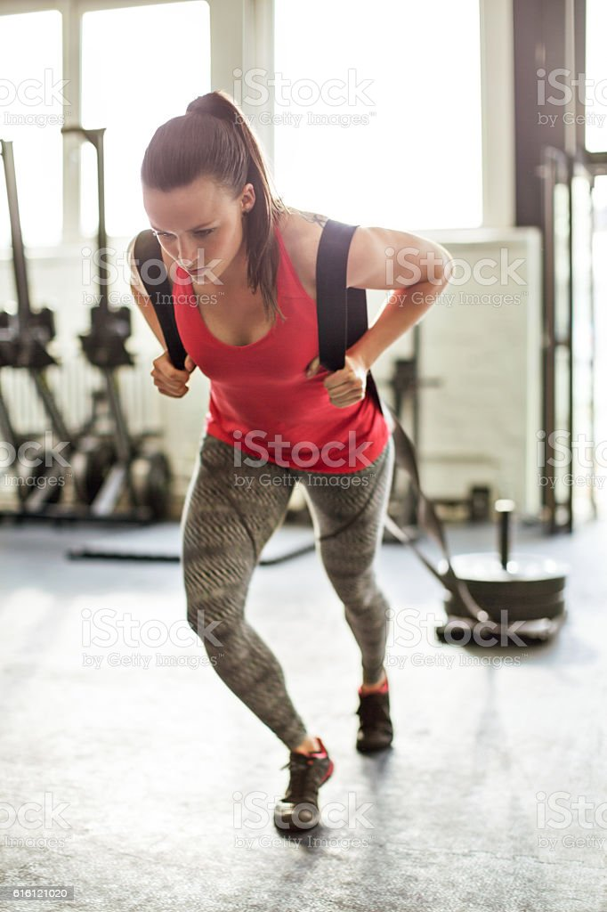 Woman pulling sled in the gym stock photo