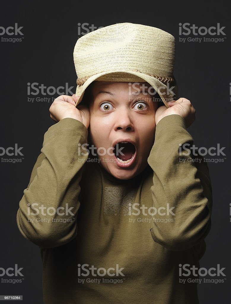 Woman pulling straw hat over her head looking scared royalty-free stock photo