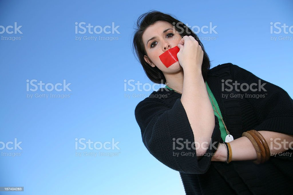 Woman pulling tape off her mouth stock photo