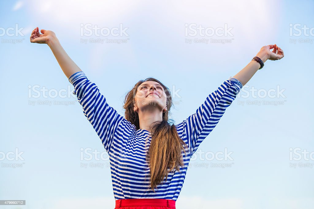 Woman pulls hands to the sunlight against the sky stock photo
