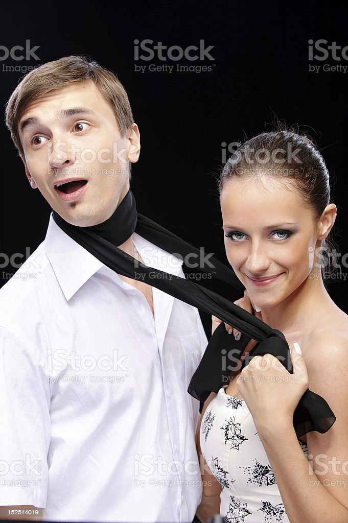 Woman pulls man for scarf royalty-free stock photo