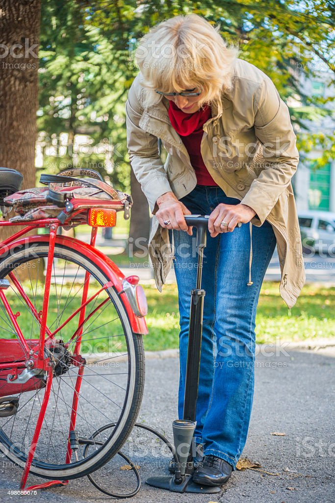 Woman Pumping Air in Bicycle Tire Outdoors stock photo