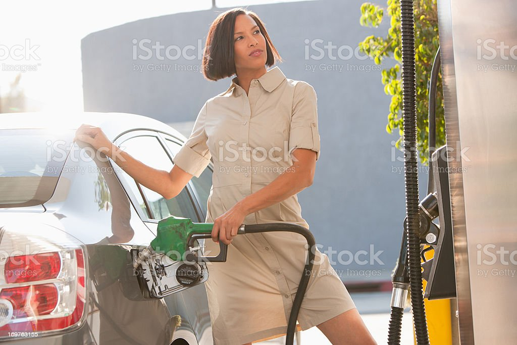 Woman pumping gas stock photo