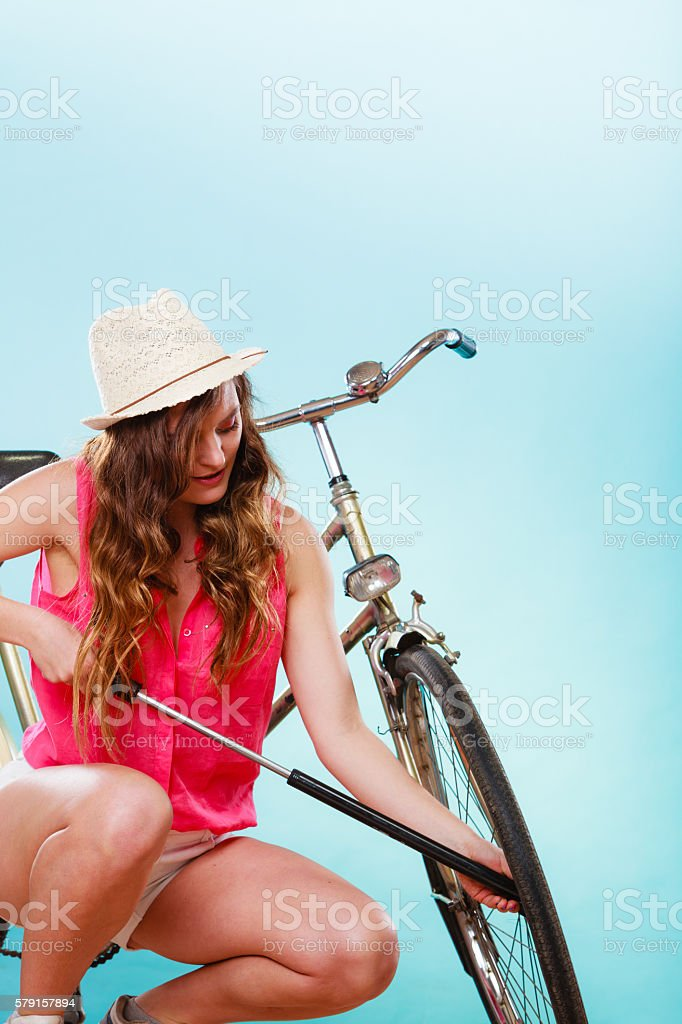 Woman pumping up tire tyre with bike pump. stock photo