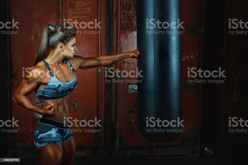 Woman punches a bag for boxing fist. stock photo