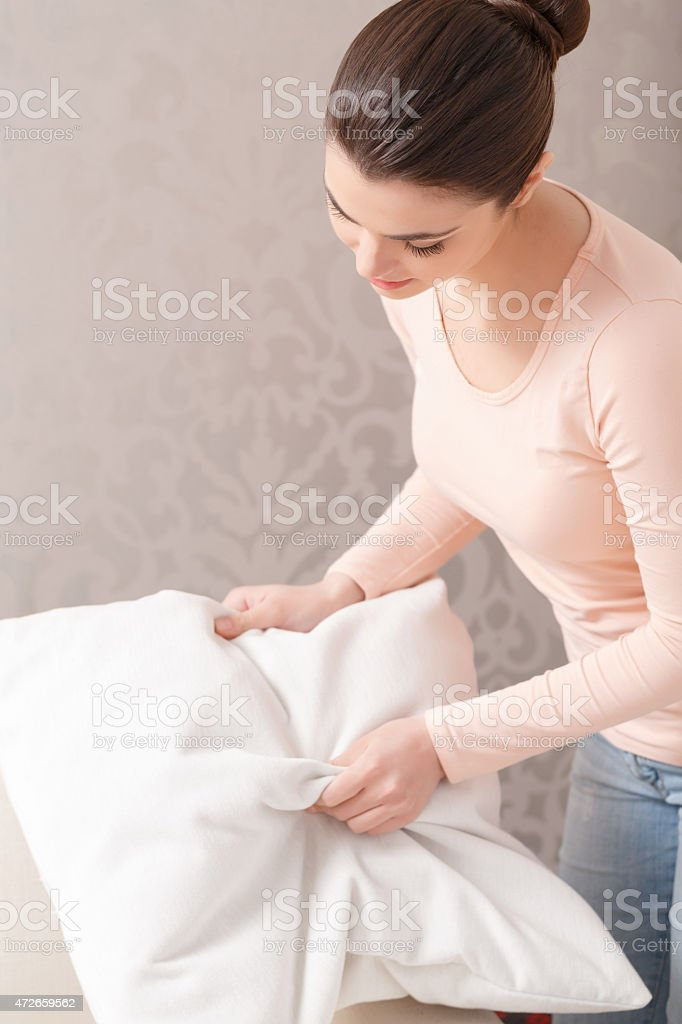 Woman punching pillow into shape stock photo