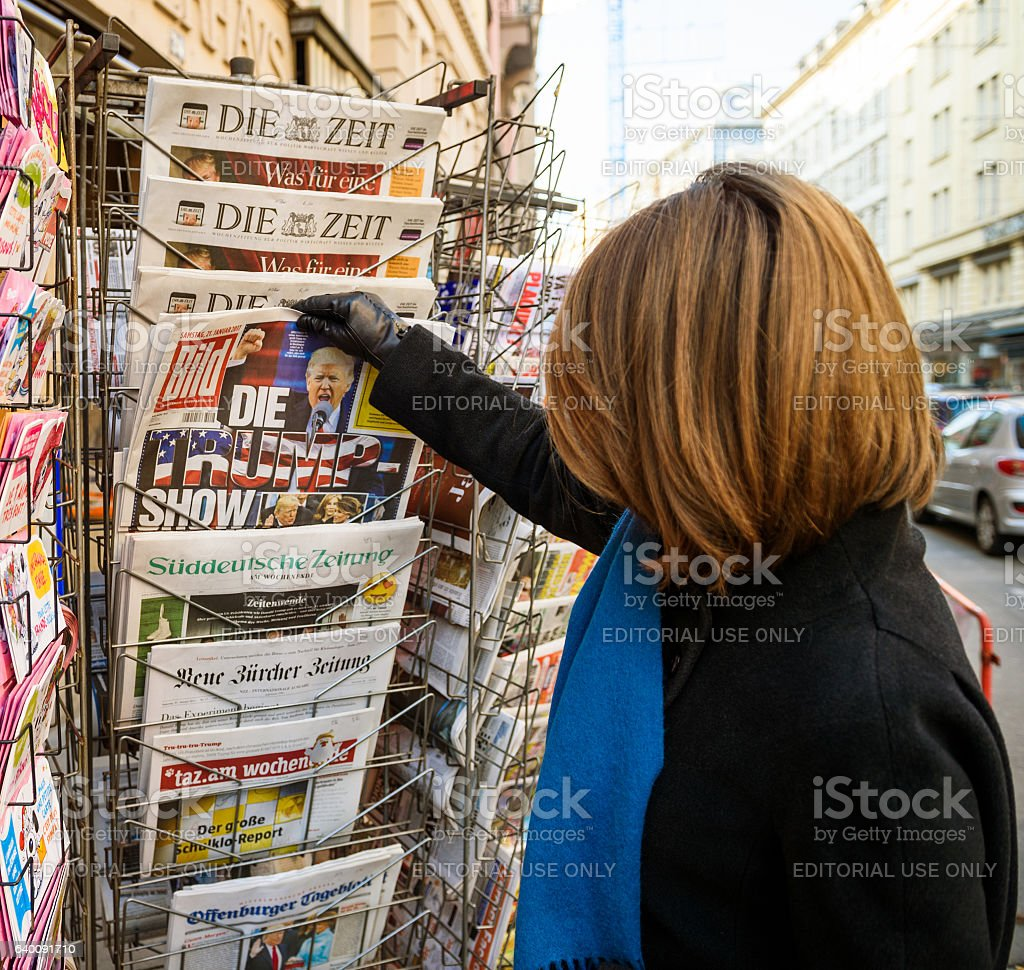 Woman purchases a bild newspaper with The Trump Show newspaper stock photo
