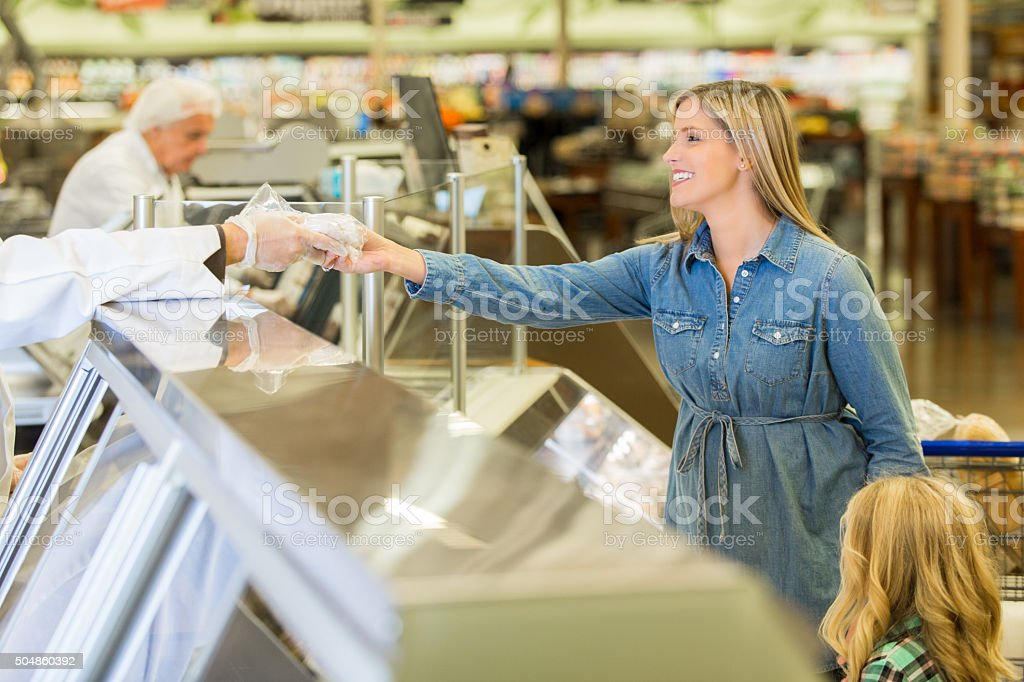 Woman purchasing meat from deli counter in supermarket stock photo