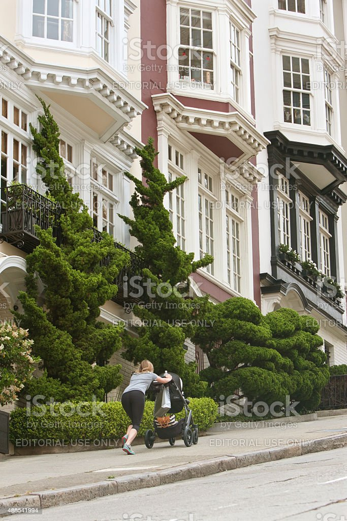 Woman Pushes Stroller Up Steep Incline In Nob Hill Area stock photo