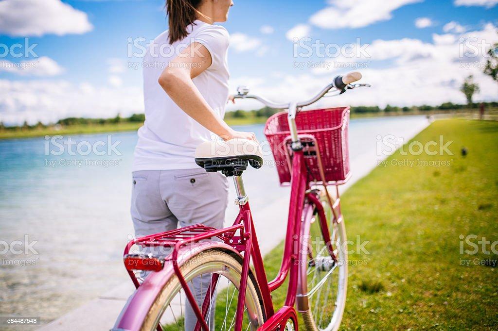 Woman pushing a bike stock photo