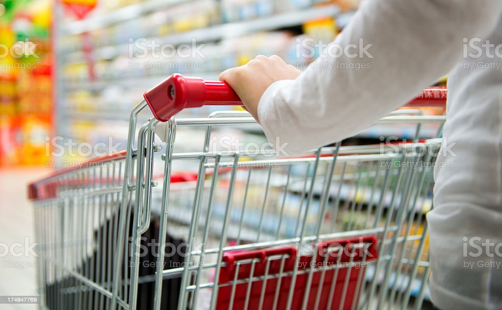 Woman pushing a grey and red shopping cart in a supermarket royalty-free stock photo