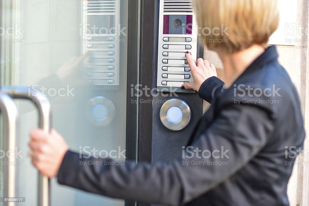 Woman pushing a intercom button stock photo