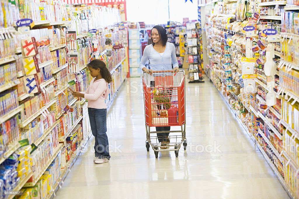 A woman pushing a shopping cart while a little girl shops stock photo