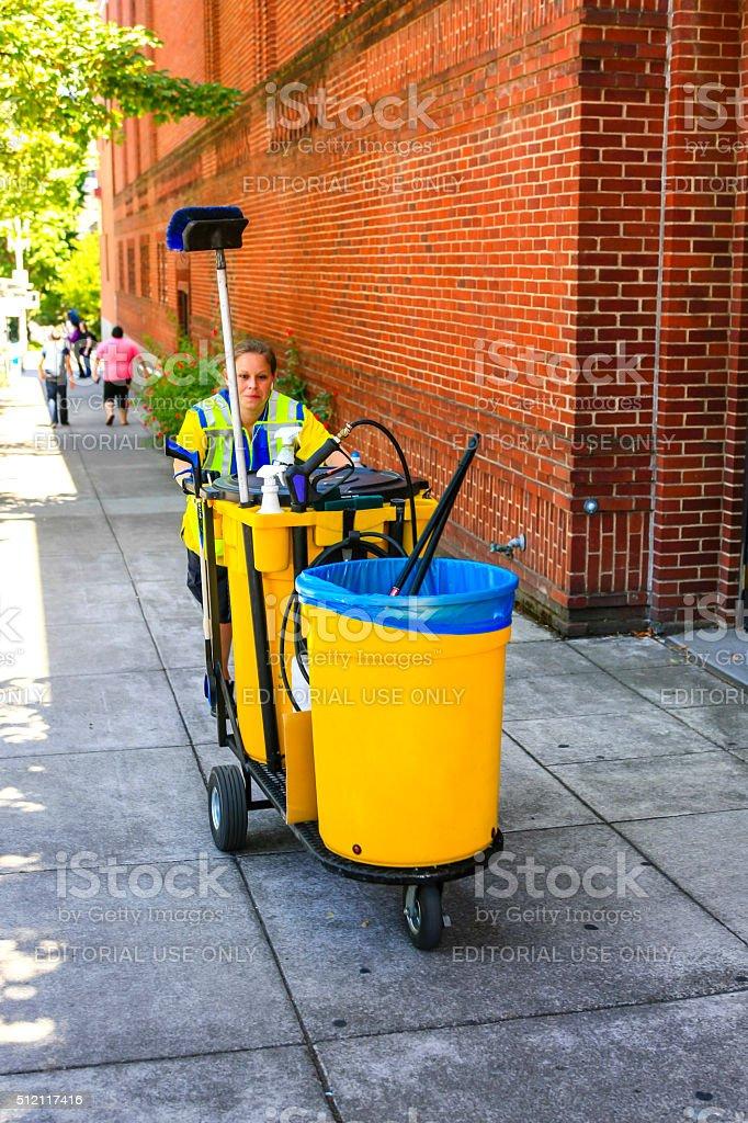 Woman pushing a street cleansing cart around Portland, Oregon stock photo