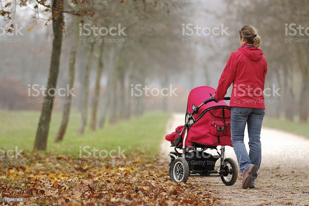 A woman pushing a stroller in a foggy park stock photo
