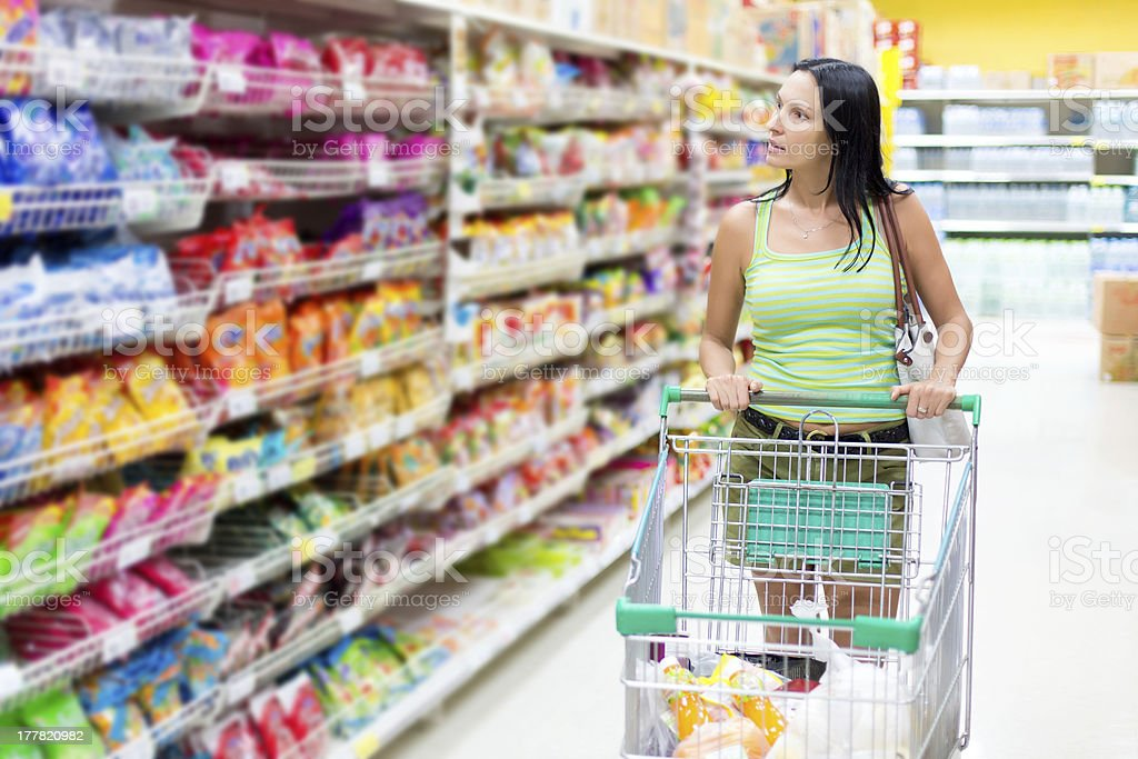Woman pushing a trolley browses the supermarket aisles royalty-free stock photo