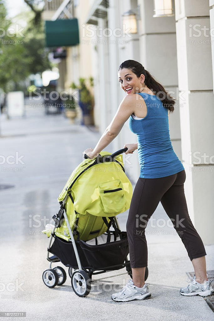 Woman pushing baby stroller stock photo