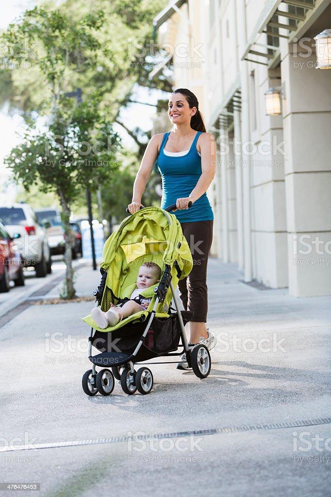 Woman pushing baby stroller royalty-free stock photo