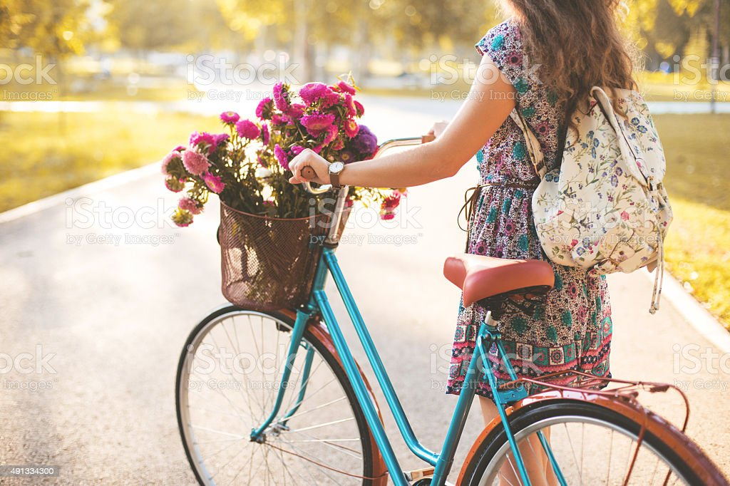 Woman pushing bicycle stock photo