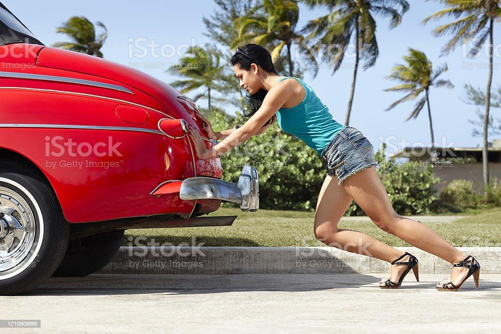 woman pushing broken down old car royalty-free stock photo