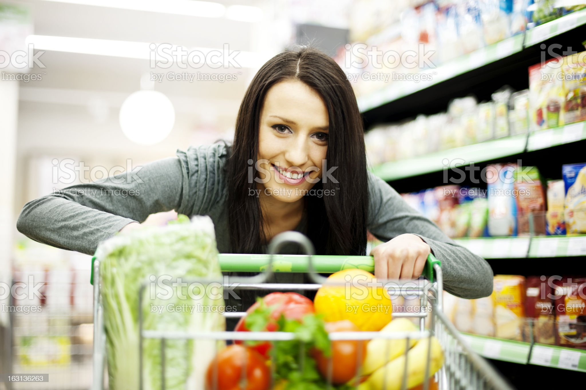 A woman pushing her cart with vegetables in the supermarket royalty-free stock photo