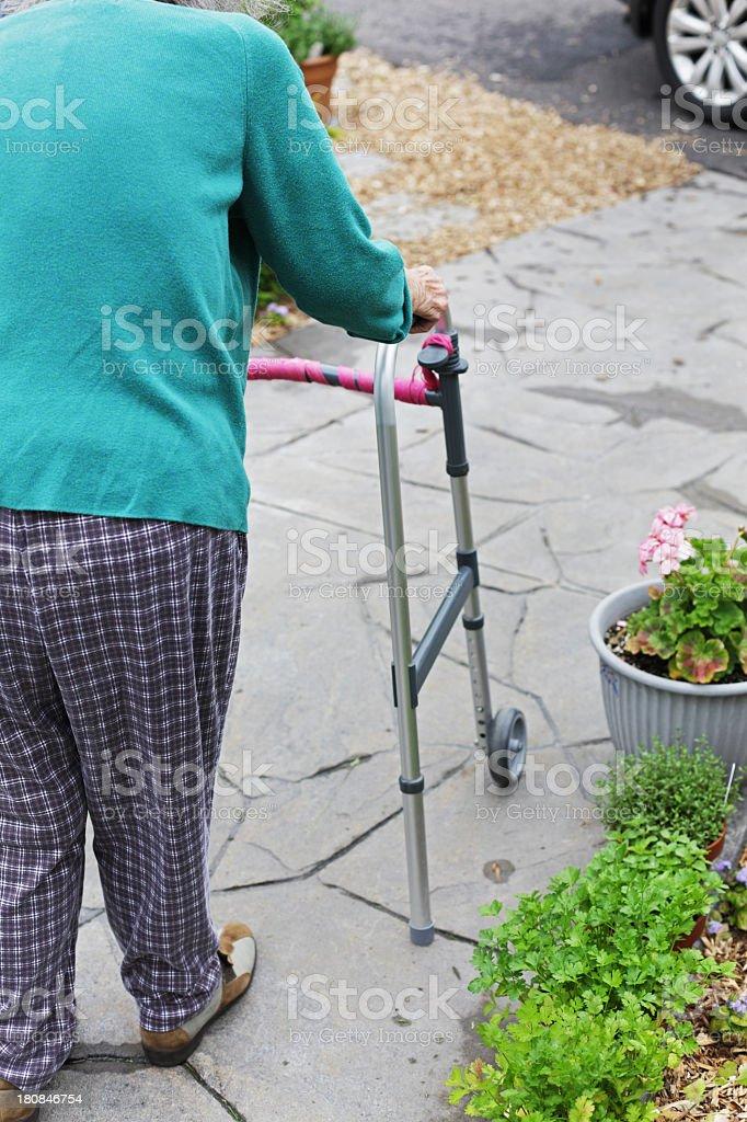 Woman Pushing Orthopedic Walker Walking to Car royalty-free stock photo