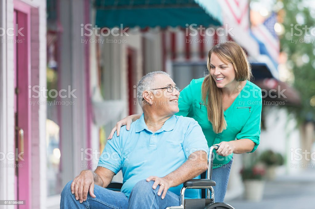 Woman pushing senior man in wheelchair, outside stores. stock photo