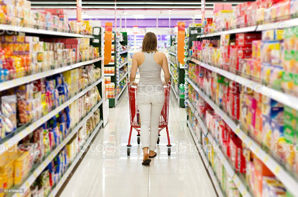 woman pushing shopping cart looking at goods in supermarket stock photo