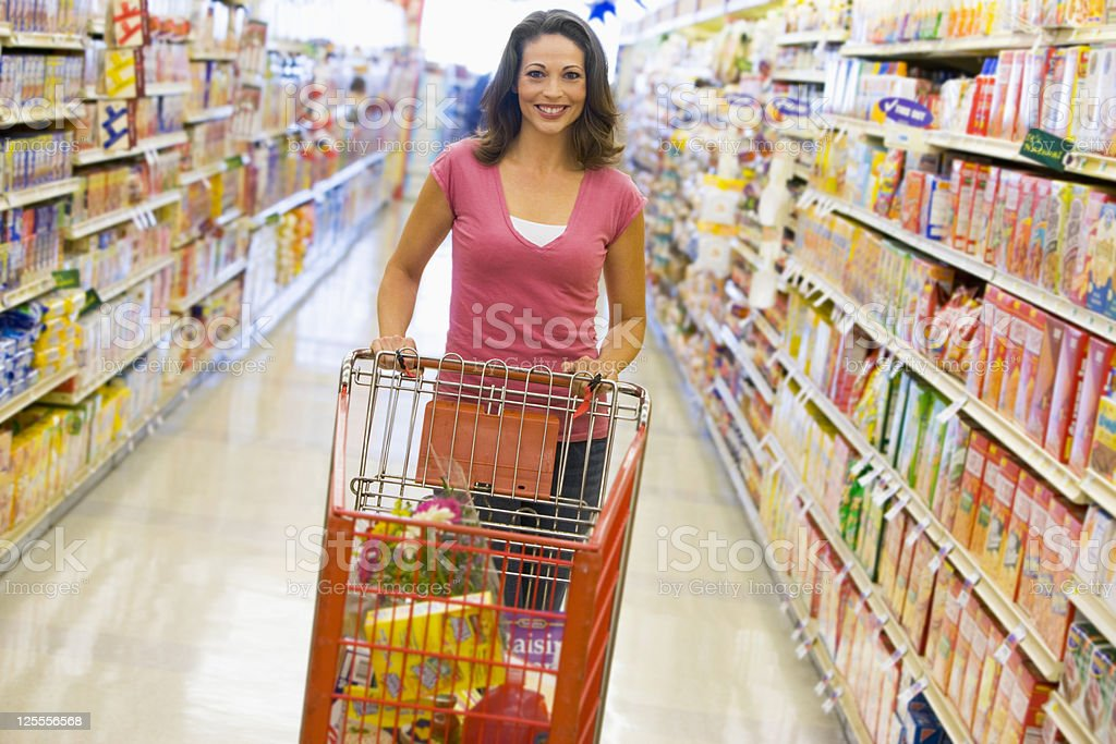 Woman pushing trolley along supermarket aisle stock photo