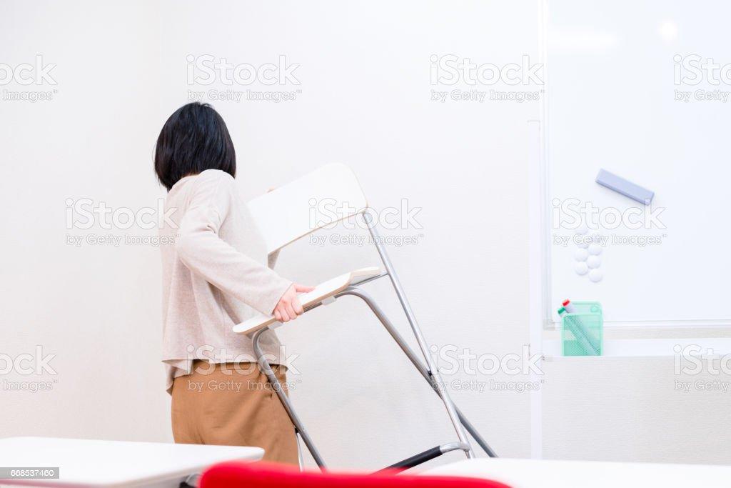 Woman put chair away stock photo