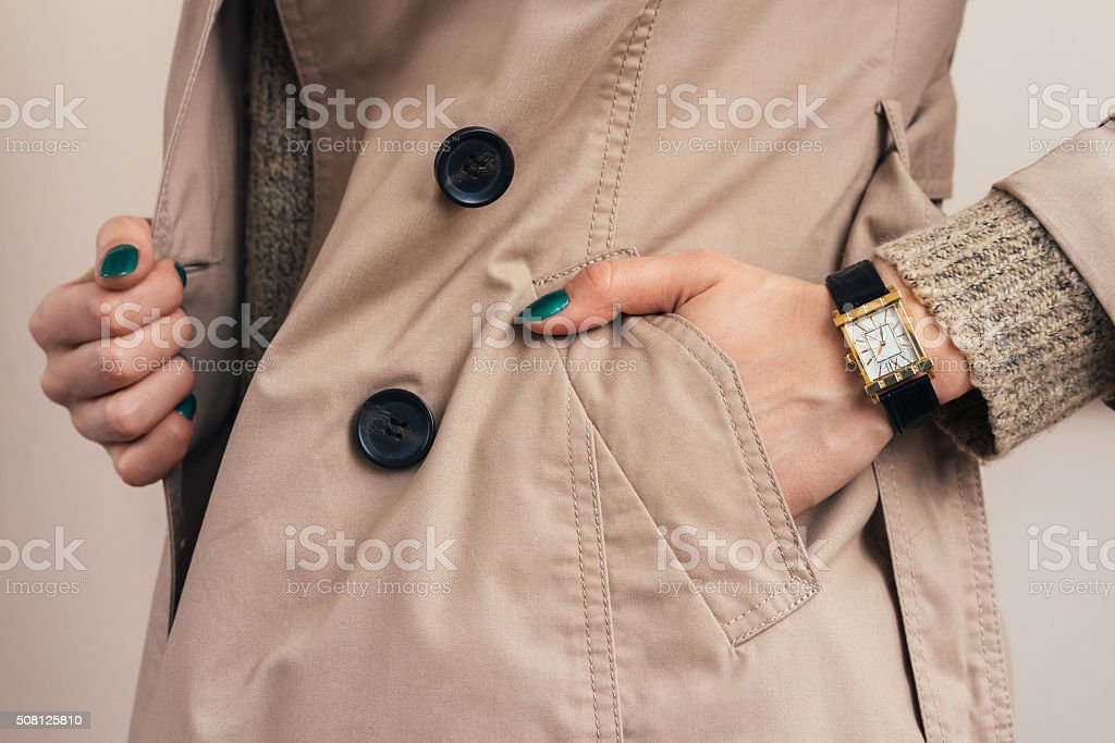 Woman put her hand in coat pocket stock photo