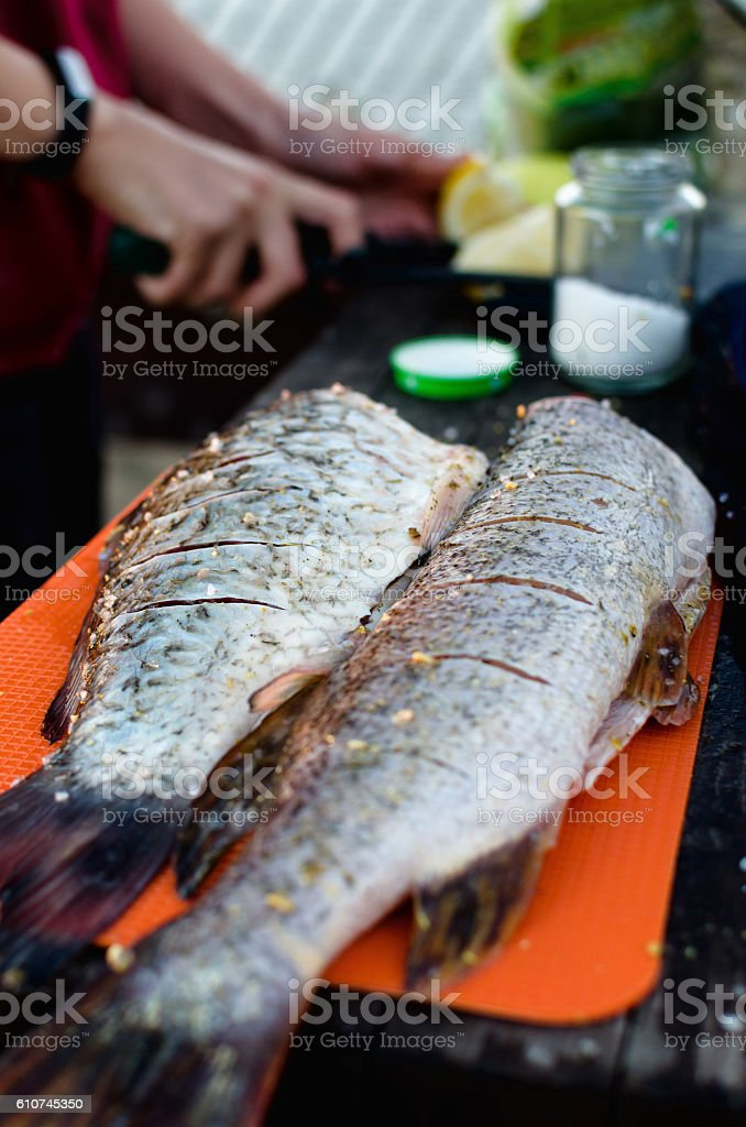 Woman put spices inside big freshly caught and gutted fish stock photo