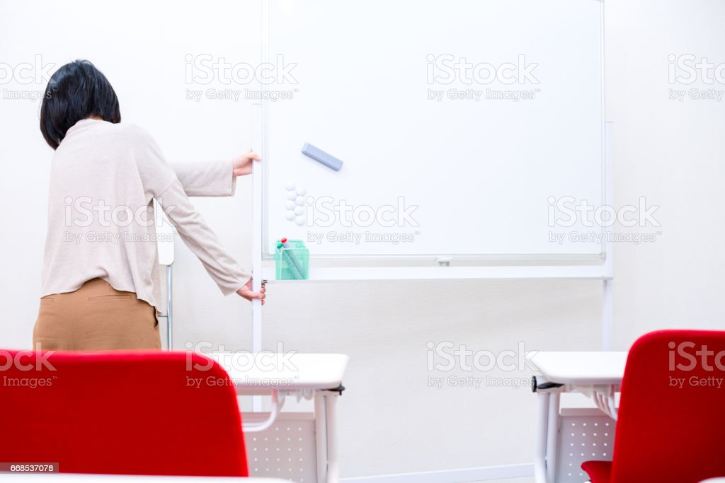 Woman put whiteboard away stock photo