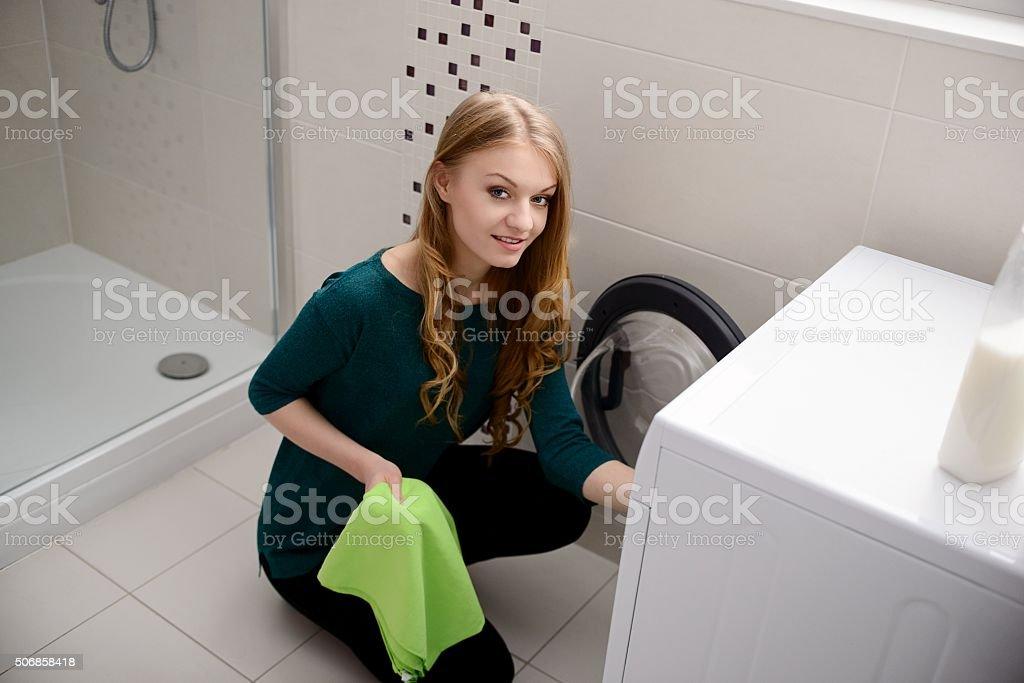 Woman puts dirty laundry into the washing machine stock photo
