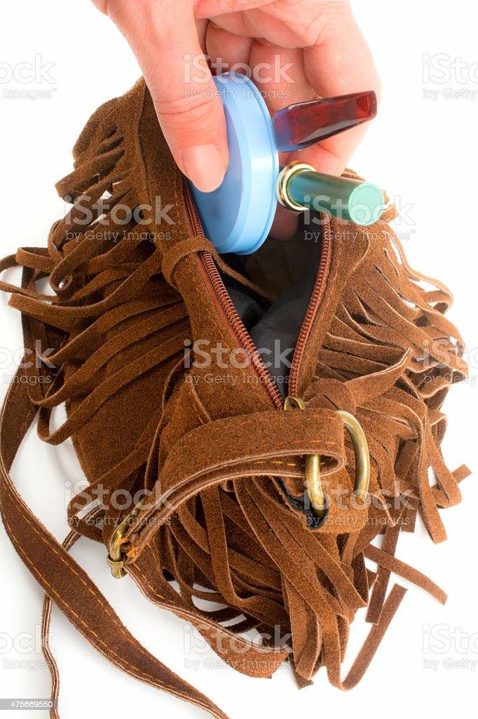 Woman puts her make up in  Brown suede fringe purse stock photo