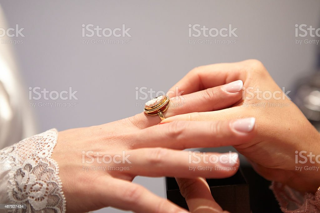 Woman putting a ring on the finger of a bride stock photo